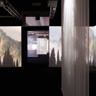 Prima sala con schermi che proiettano immagini di paesaggi naturalistici.